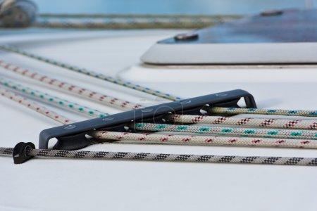 Photo pour Détails du voilier. Cordes de couleur sur pont blanc - image libre de droit