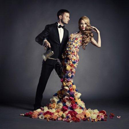 Photo pour Jeune homme verse de l'arrosage peut une belle dame en robe de fleur - image libre de droit