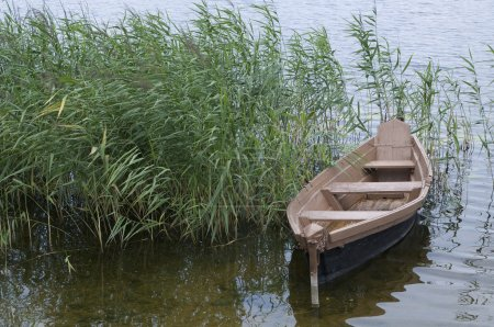 Wooden boat over the riverside of lake...