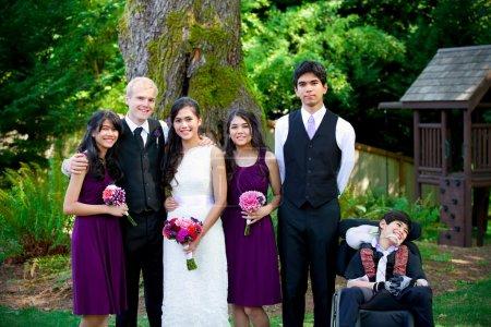 Photo pour Mariage interracial. Groom debout avec les frères et sœurs de sa mariée biraciale à l'extérieur. Le plus jeune garçon est handicapé avec une paralysie cérébrale . - image libre de droit