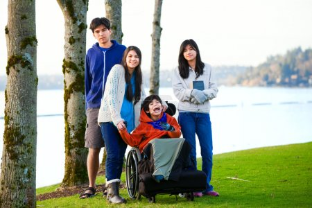 Behinderter kleiner Junge im Rollstuhl von Bruder und Schwester umgeben