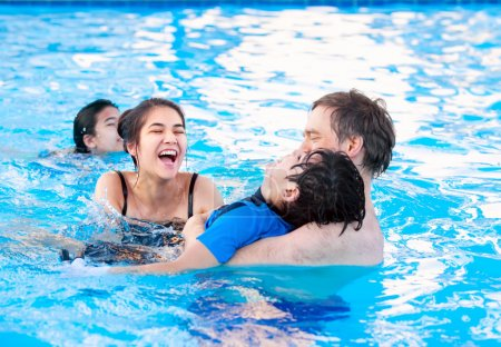 Multiracial family swimming together in pool. Disabled youngest