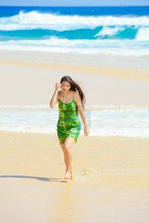 Photo pour Belle fille de l'adolescence dans la robe verte marchant le long de la plage hawaïenne au bord de l'eau - image libre de droit
