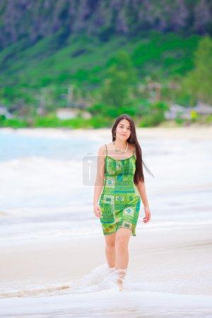 Photo pour Belle adolescente en robe verte marchant le long de la plage hawaïenne au bord de l'eau - image libre de droit