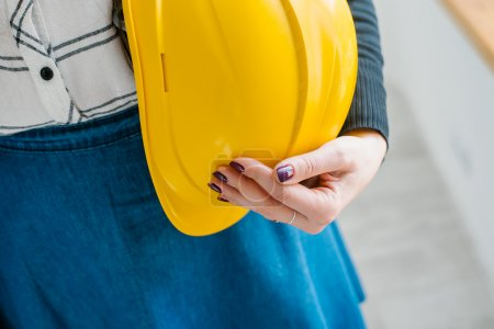 girl holding a construction helmet