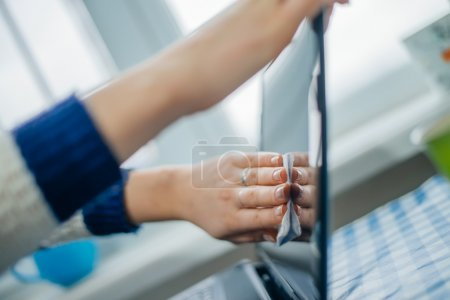 Close up of woman hand cleaning laptop screen with...