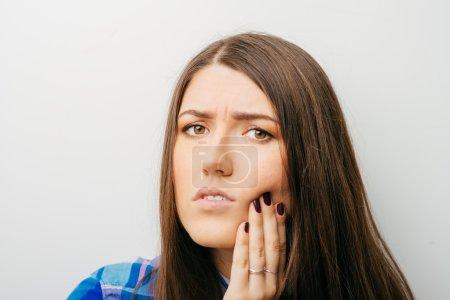 Photo pour Jeune femme pressant sa joue meurtrie avec une expression douloureuse comme si elle avait un terrible mal de dent . - image libre de droit