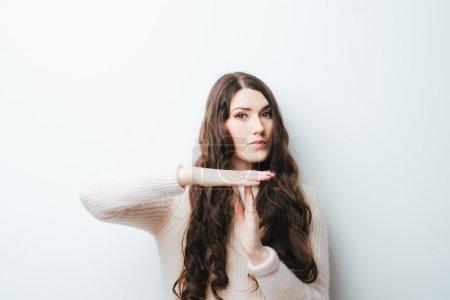 Photo pour Belle brune aux cheveux longs demande du temps mort sur un fond blanc - image libre de droit