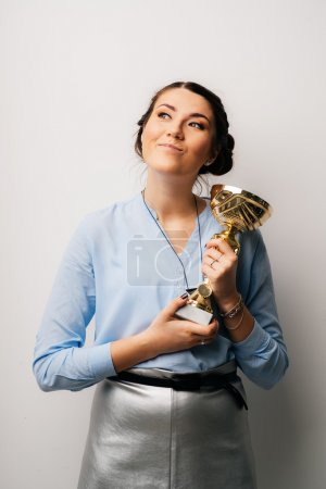 woman holding a prize cup