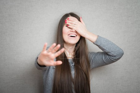 Photo for Young brunette woman laughing and covering her face with hand - Royalty Free Image