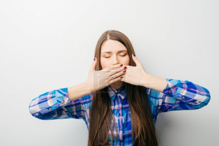 girl covers her mouth with hands