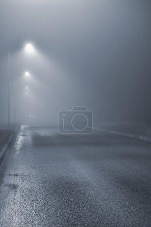 Photo pour Réverbères, nuit brumeuse brumeuse, lanternes de lampadaires, route déserte dans le brouillard, goudron d'asphalte humide, phares de voiture approchant, verticale, clé bleue - image libre de droit