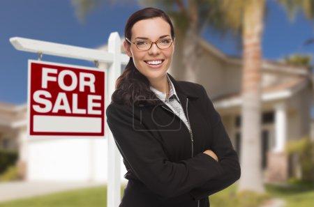 Foto de Atractiva mujer de raza mixta en frente de la casa y en venta . - Imagen libre de derechos