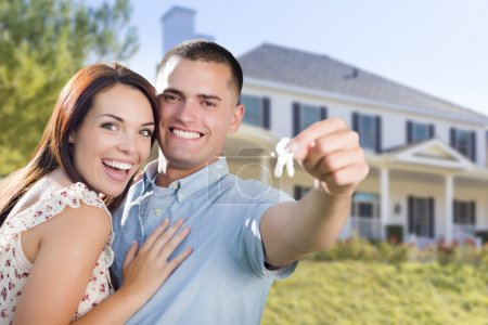 Photo for Mixed Race Excited Military Couple In Front of New Home Showing Off Their House Keys. - Royalty Free Image