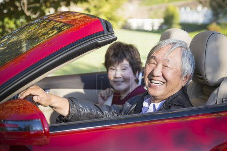 Happy Chinese Couple Enjoying An Afternoon Drive in Their Conver