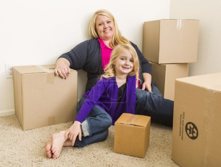 Photo for Happy Young Mother and Daughter In Empty Room With Moving Boxes. - Royalty Free Image