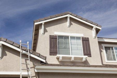 Leiter lehnt an einem frisch gestrichenen Haus