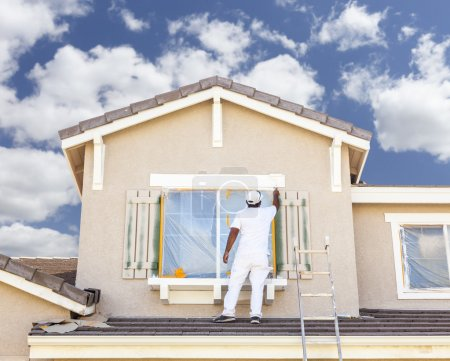House Painter Painting the Trim And Shutters of Home