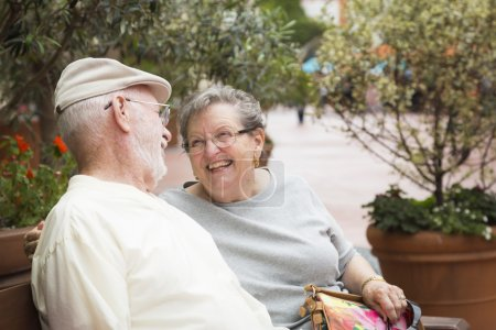 Foto de Happy Senior Couple Resting on a Bench in the Market Place. - Imagen libre de derechos