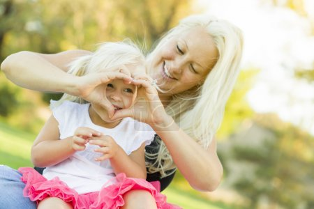 Photo for Cute Little Girl With Mother Making Heart Shape with Hands Outdoors. - Royalty Free Image