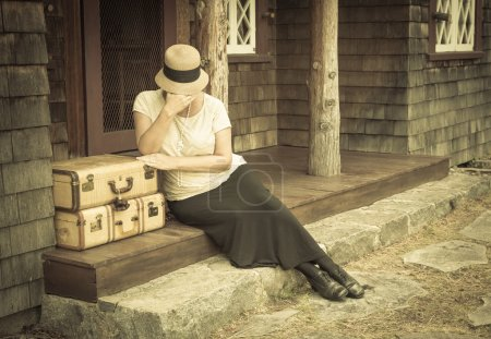 Distressed 1920s Girl Near Suitcases on Porch with Vintage Effec