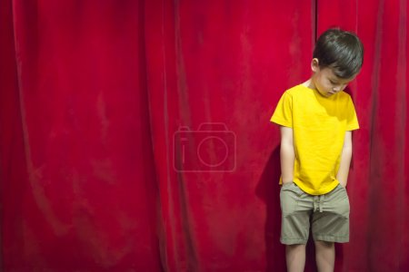 Pouting Mixed Race Boy Standing In Front of Red Curtain