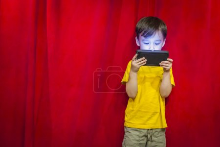 Mixed Race Boy Watching Cell Phone in Front of Curtain