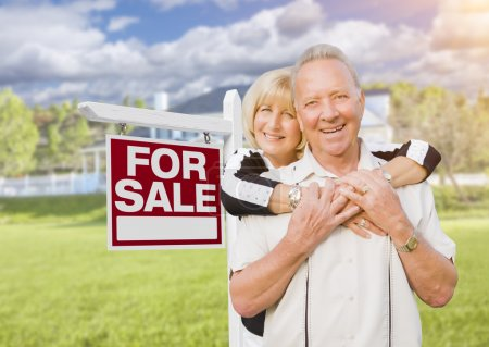 Happy Senior Couple Front of For Sale Sign and House