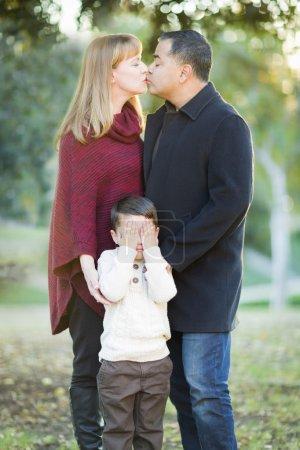 Photo pour Amour Couple de Race Mix baiser comme jeune fils cache ses yeux. - image libre de droit