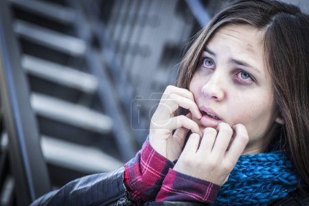 Young Bruised and Frightened Girl on Staircase