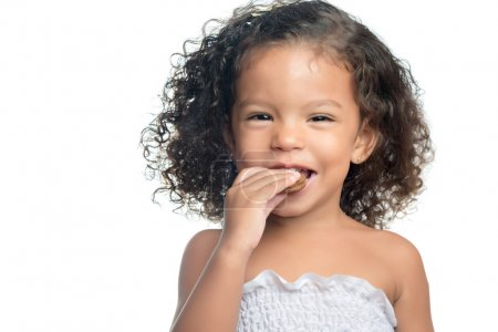 Photo for Joyful little girl with an afro hairstyle eating a chocolate cookie isolated on white - Royalty Free Image