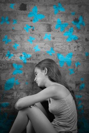 Sad teenage girl with blue butterflies