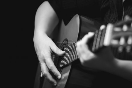 Photo for Acoustic guitar detail - Musician's hands playing a classic guitar isolated on black - Royalty Free Image