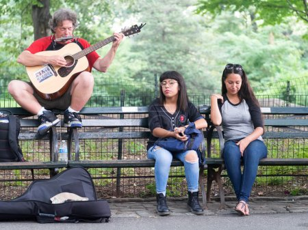 Photo for NEW YORK,USA - AUGUST 21,2015 : Street performer singing John Lennon songs at Strawberry Fields in Central Park - Royalty Free Image