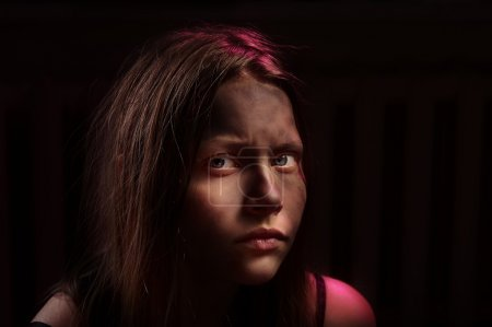 Photo for Dirty frightened teenage girl sits locked in a dark room - Royalty Free Image
