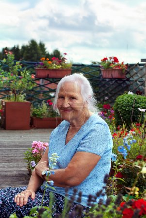 Photo pour Portrait de la femme âgée souriante, dans un jardin - image libre de droit