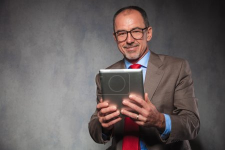 businessman holding his tablet while posing