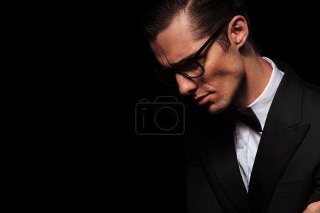 Photo for Side portrait of classy elegant man in black suit posing in dark studio background looking down - Royalty Free Image