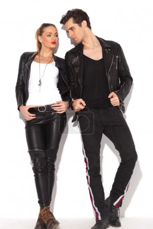 Photo pour Young fashion couple in leather clothes looking at each other, full body picture, leaning on a white wall - image libre de droit
