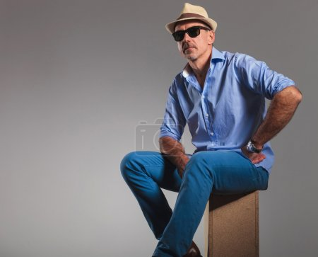 mature man in jeans wearing hat and sunglasses while seated