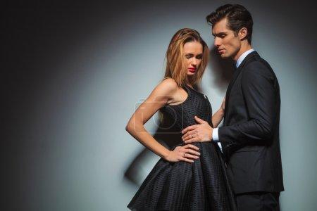 couple in black posing embraced in studio