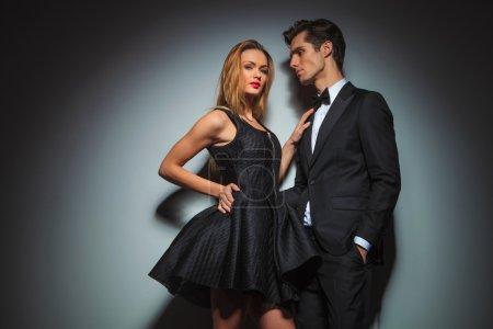 elegant couple in black embracing in gray studio