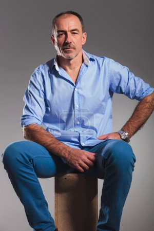 portrait of seated mature bearded man in jeans