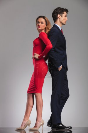 young elegant couple standing back to back in studio