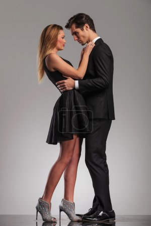 Photo for Happy elegant couple standing embraced and looking at each other on grey studio background - Royalty Free Image