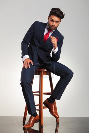 serious business man in elegant double breasted suit sitting
