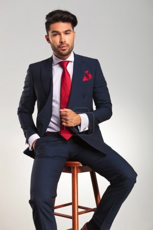 elegant man in suit and tie sitting on a stool