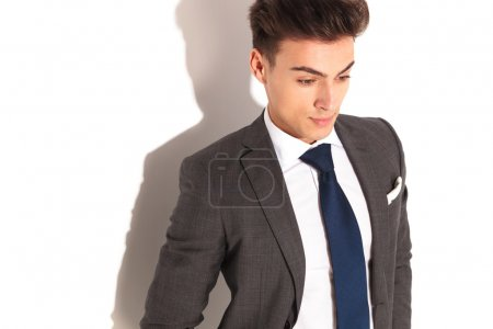 business man in suit and tie looking down