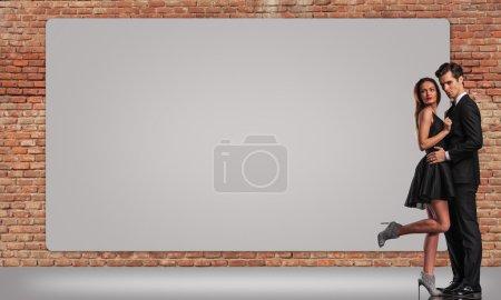 elegant young couple standing embraced near big billboard