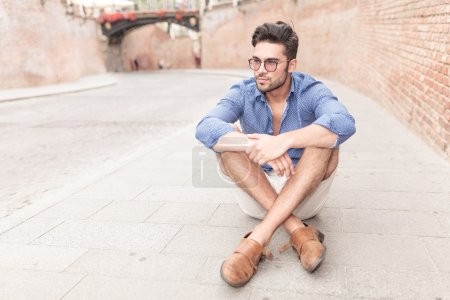 Photo for Casual young man looks away while sitting on the sidewalk in the city - Royalty Free Image